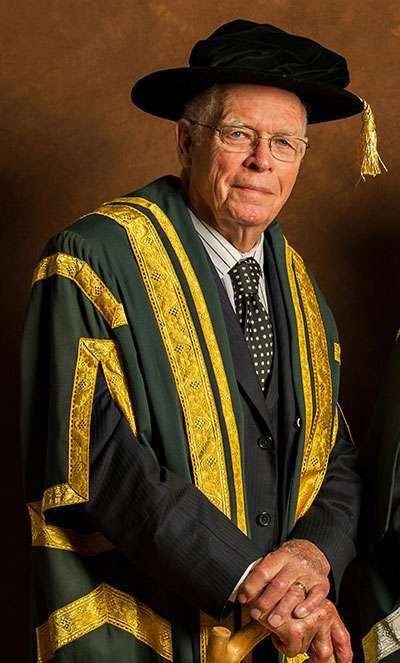 Portrait photo of Dr. Edward J. Conroy, Huntington University Chancellor Emeritus. In this photo Dr. Conroy is seen wearing his official Chancellor Emeritus hat and robe (green and gold)..