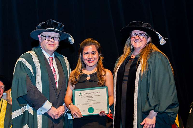Photo of Dr. Kevin McCormick, Huntington University President and Vice-Chancellor, and Mary-Liz Warwick, Huntington University Board Chair, presenting student Abegail Villaruel with the Margaret Kingsburg Smith Scholarship in Gerontology