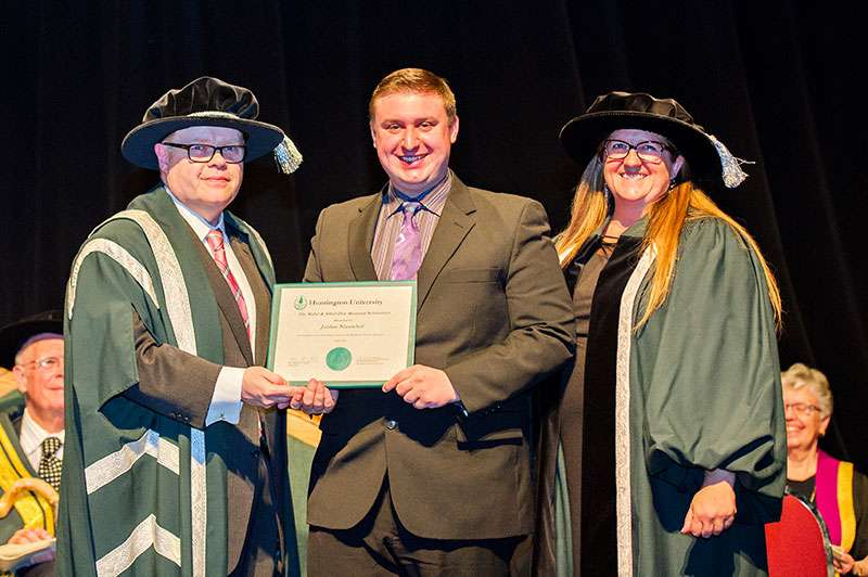Photo of Dr. Kevin McCormick, Huntington University President and Vice-Chancellor, and Mary-Liz Warwick, Huntington University Board Chair, presenting student Jordan Nieuwhof with the Mabel and Alfred Dew Memorial Scholarship