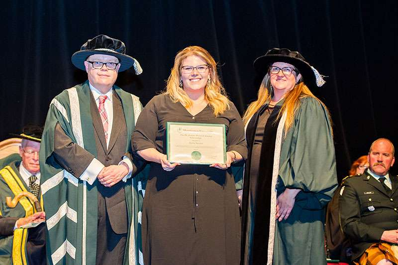 Photo of Dr. Kevin McCormick, Huntington University President and Vice-Chancellor, and Mary-Liz Warwick, Huntington University Board Chair, presenting student Taylor Squires with the Dr. Jeanne Warwick Conroy Scholarship